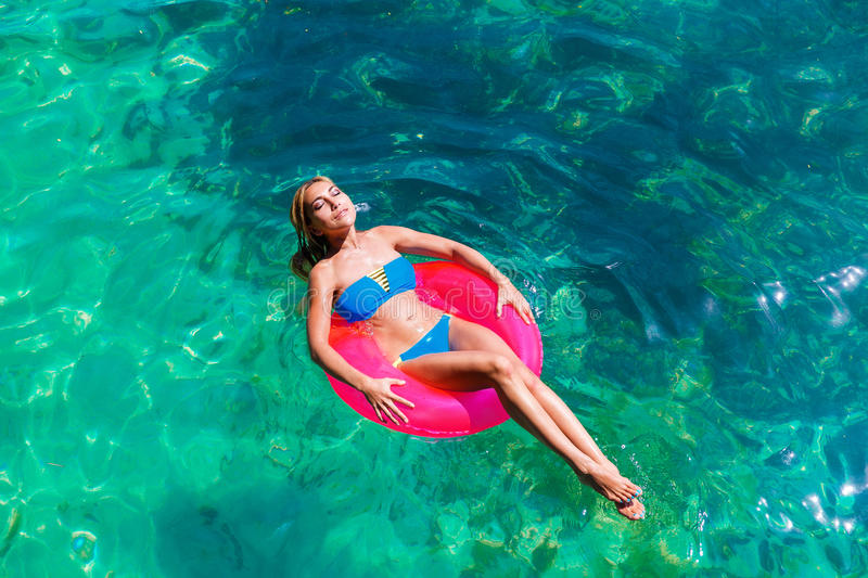 Young beautiful girl in bikini swims in a tropical sea on a rubber ring. Summer vacation concept. royalty free stock images