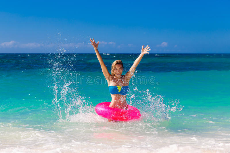 Young beautiful girl in bikini swims in a tropical sea on a rubber ring. Summer vacation concept. stock photography