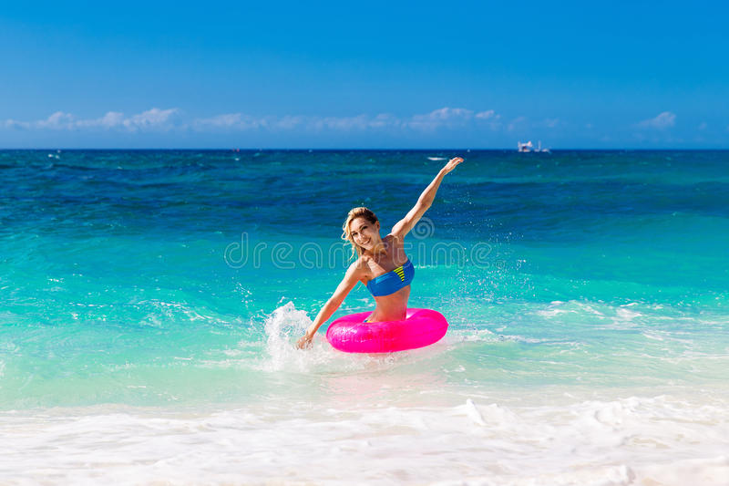 Young beautiful girl in bikini swims in a tropical sea on a rubber ring. Summer vacation concept. stock image