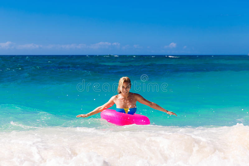 Young beautiful girl in bikini swims in a tropical sea on a rubber ring. Summer vacation concept. royalty free stock image