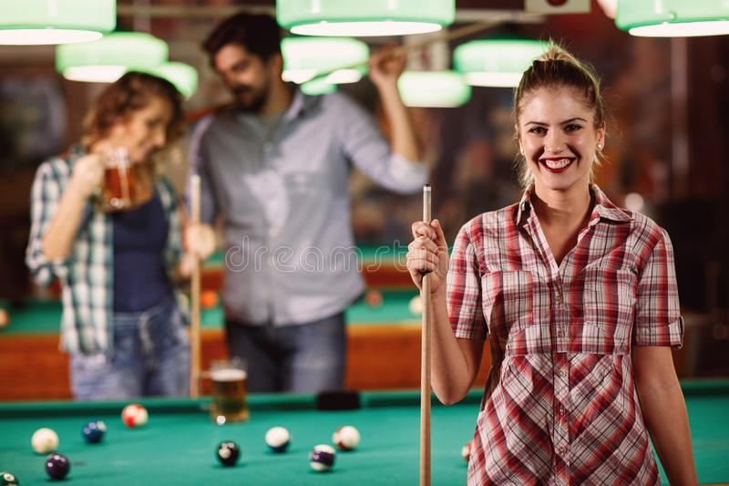 Young beautiful girl in billiard club with cue stick stock image
