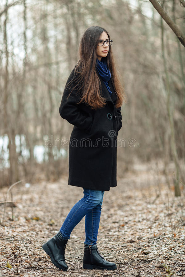a8e258d24 Young Beautiful Girl In A Black Coat Blue Scarf Glasses Walking In ...