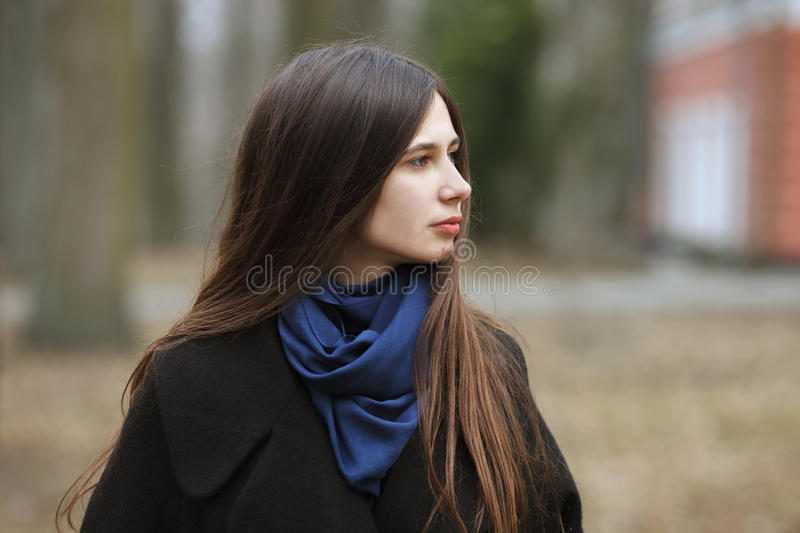 Young beautiful girl in a black coat and blue scarf for a walk in the autumn / spring park. An elegant brunette girl with gorgeous. Extra long hair. Lifestyle royalty free stock photos