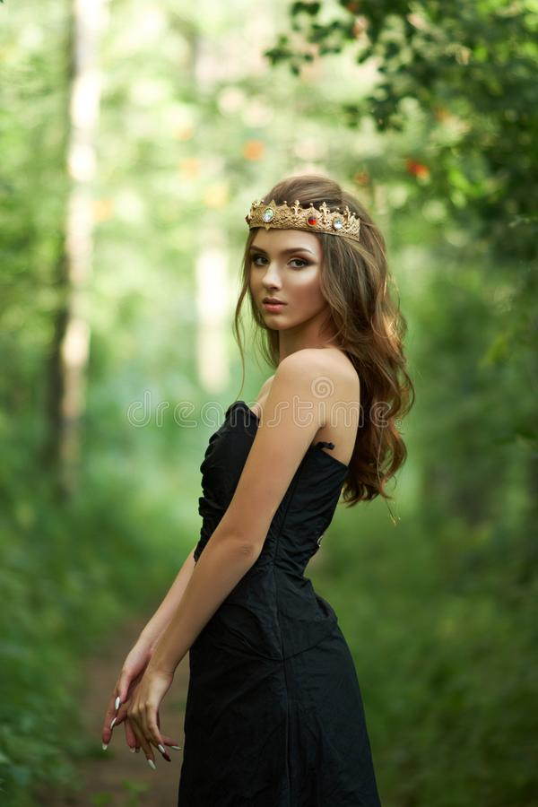 Young, beautiful girl in a black dress with a crown stock photos