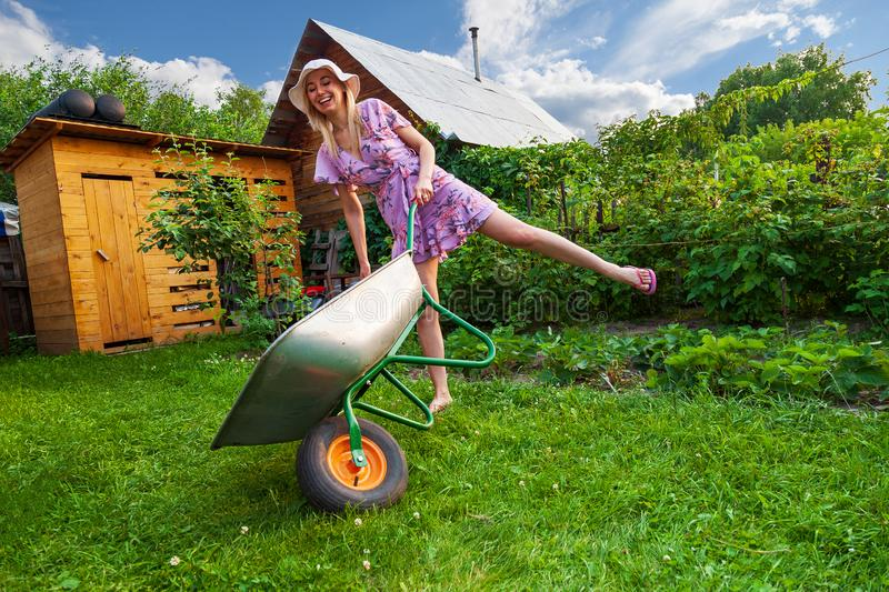Young beautiful girl blonde in a dress and hat, having fun in the garden holding in her hands a green cart on the lawn with grass royalty free stock photography