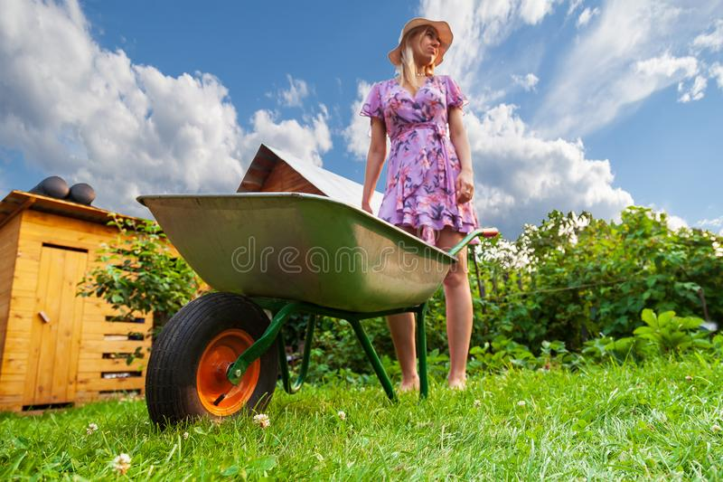 Young beautiful girl blonde in a dress and hat, having fun in the garden holding in her hands a green cart and looking to the side stock image