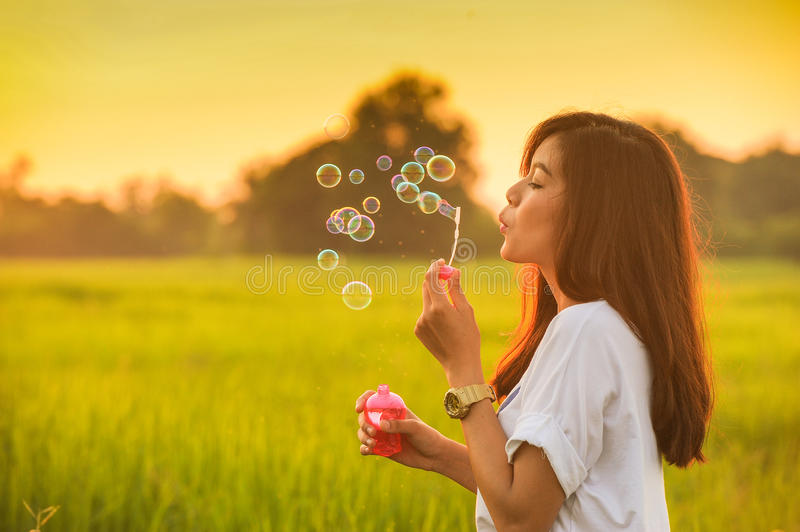 Young beautiful girl blowing bubbles royalty free stock photography