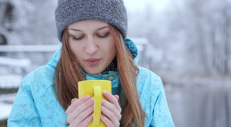 Young beautiful girl blowing on a hot tea or coffee standing on the shore of a winter lake. stock photography