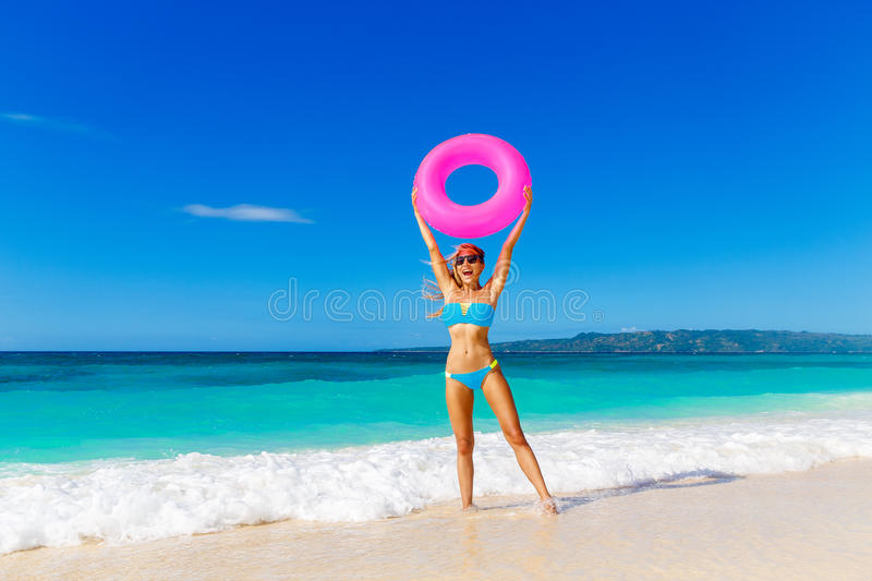 Young beautiful girl in blue bikini having fun on a tropical beach with rubber ring for swimming. Blue sea and sky in. The background. Summer vacation concept royalty free stock photos