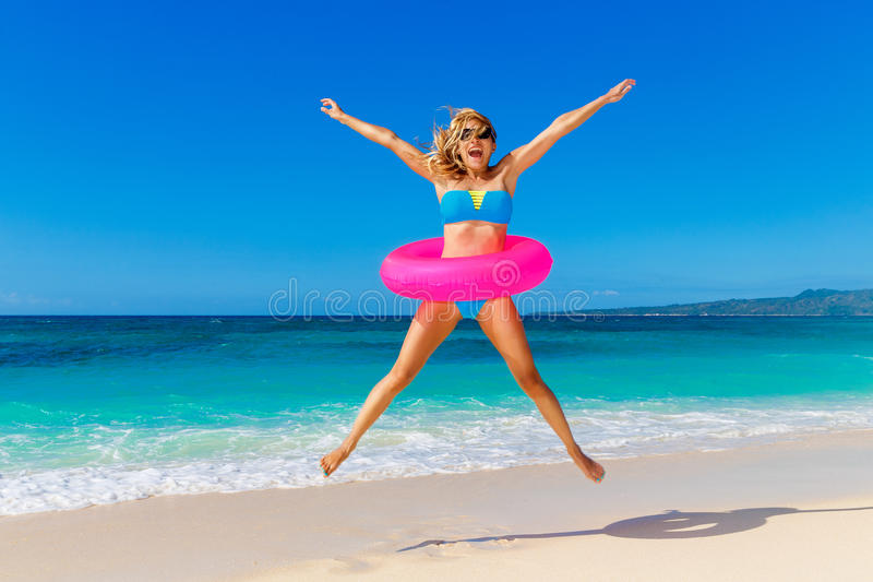 Young beautiful girl in blue bikini having fun on a tropical beach with rubber ring for swimming. Blue sea and sky in stock images