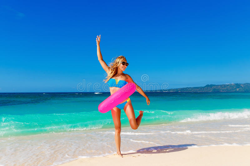 Young beautiful girl in blue bikini having fun on a tropical beach with rubber ring for swimming. Blue sea and sky in stock photography