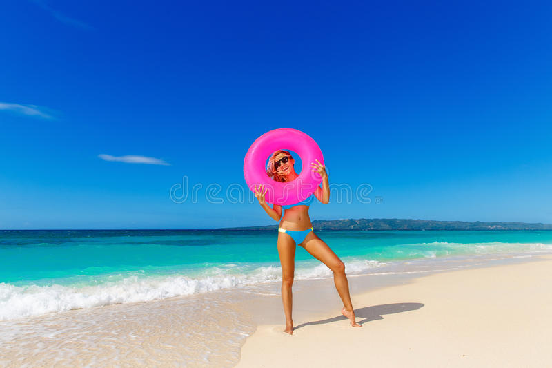 Young beautiful girl in blue bikini having fun on a tropical beach with rubber ring for swimming. Blue sea and sky in royalty free stock image