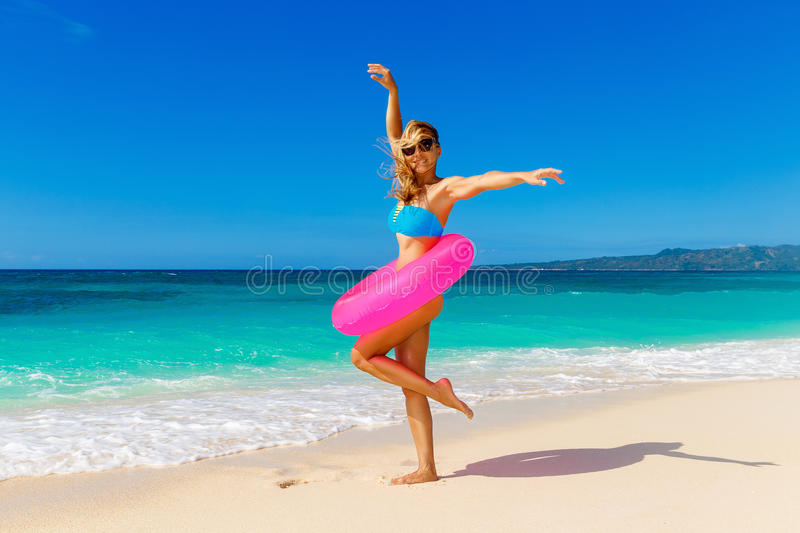Young beautiful girl in blue bikini having fun on a tropical beach with rubber ring for swimming. Blue sea and sky in royalty free stock photography