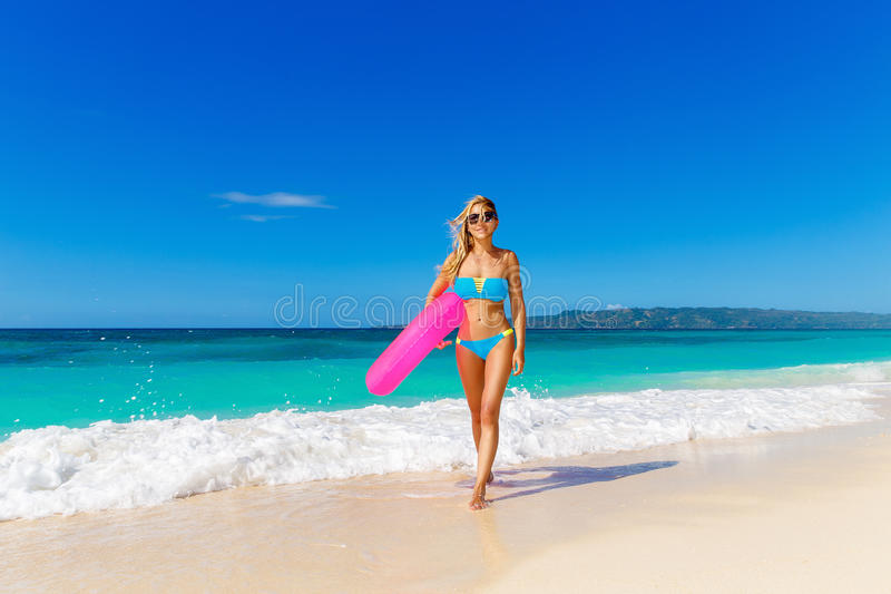 Young beautiful girl in blue bikini having fun on a tropical beach with rubber ring for swimming. Blue sea and sky in stock photo