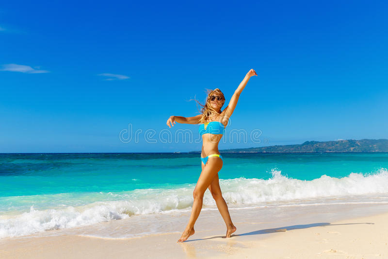 Young beautiful girl in blue bikini having fun on a tropical beach. Blue sea and sky in the background. Summer vacation concept. stock photos