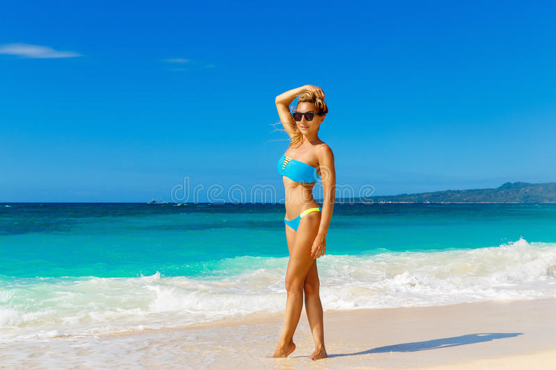 Young beautiful girl in blue bikini having fun on a tropical beach. Blue sea and sky in the background. Summer vacation concept. royalty free stock photography