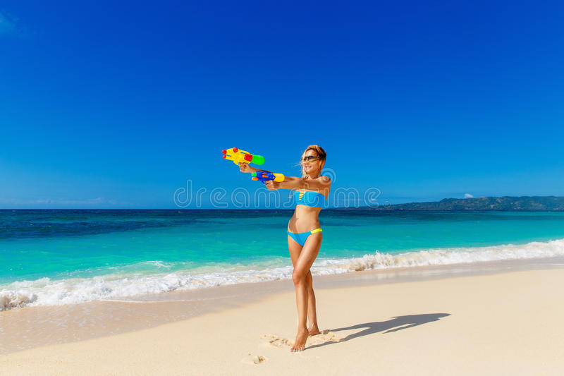 Young beautiful girl in blue bikini having fun on a tropical beach with toy water guns. Blue sea and sky in the background. stock photography