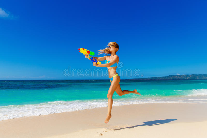 Young beautiful girl in blue bikini having fun on a tropical beach with toy water guns. Blue sea and sky in the background. royalty free stock photos
