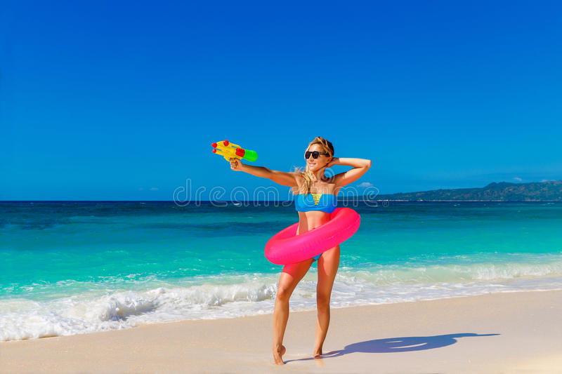 Young beautiful girl in blue bikini having fun on a tropical beach with toy water guns. Blue sea and sky in the background. royalty free stock images
