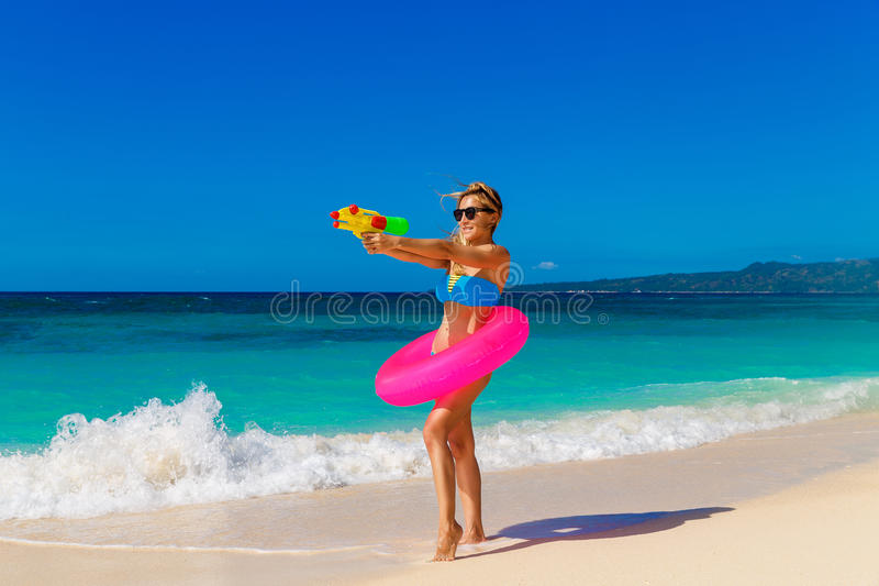 Young beautiful girl in blue bikini having fun on a tropical beach with toy water guns. Blue sea and sky in the background. royalty free stock photography