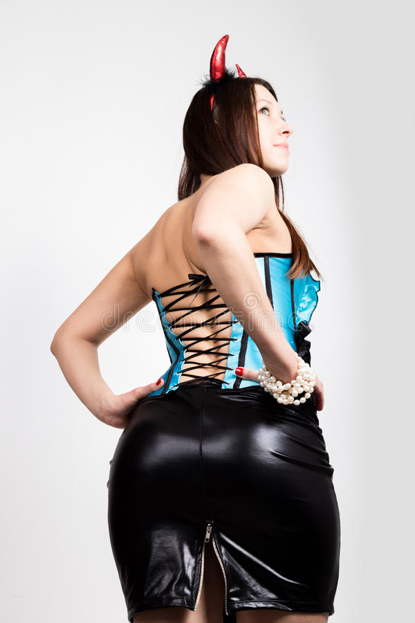 Young beautiful girl in blue corset with red horns looks like pretty Devil stock image