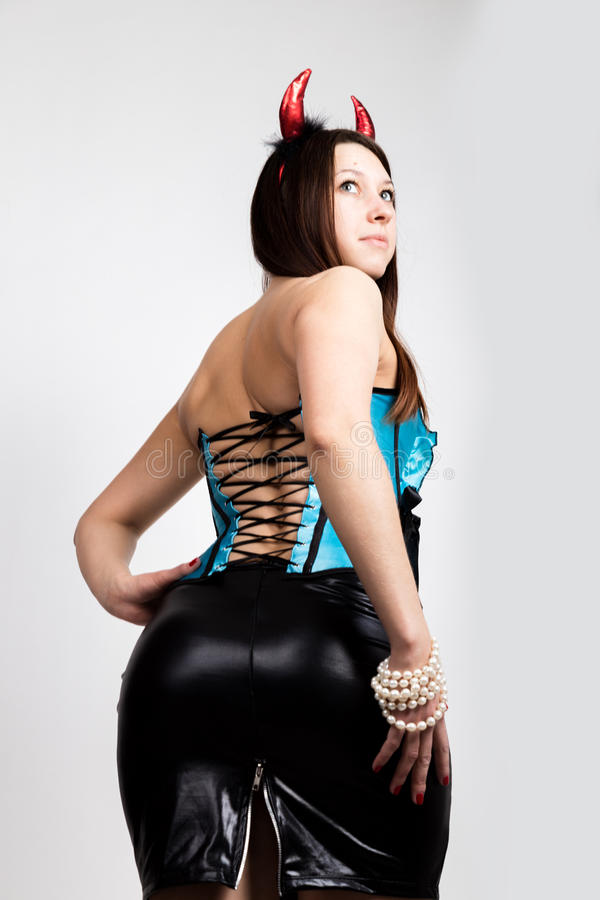 Young beautiful girl in blue corset with red horns looks like pretty Devil stock photos