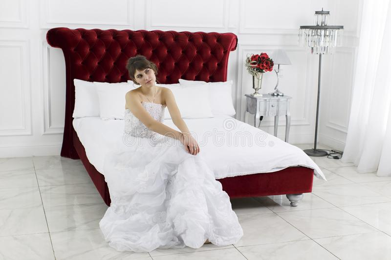 Young beautiful girl in a bride`s dress sits stock images