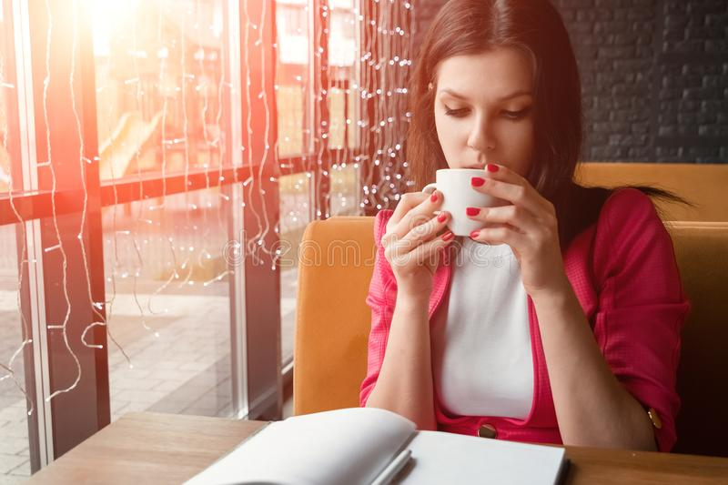 Young beautiful girl, businesswoman drinking tea or coffee sitting in cafe. Business lunch, break royalty free stock photography