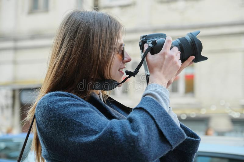 Young beautiful girl with camera in the spring city, girl tourist taking photographs on city street stock image
