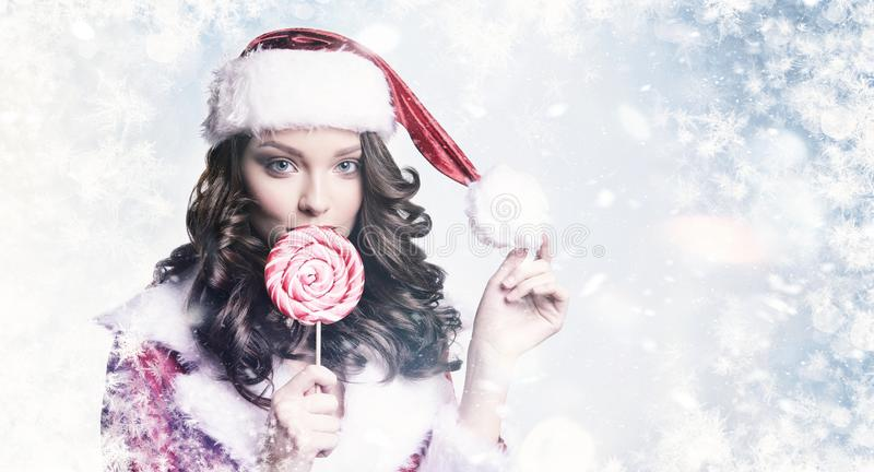 Young beautiful girl with candy on snowy winter background. Christmas and New Year holidays concept. royalty free stock images