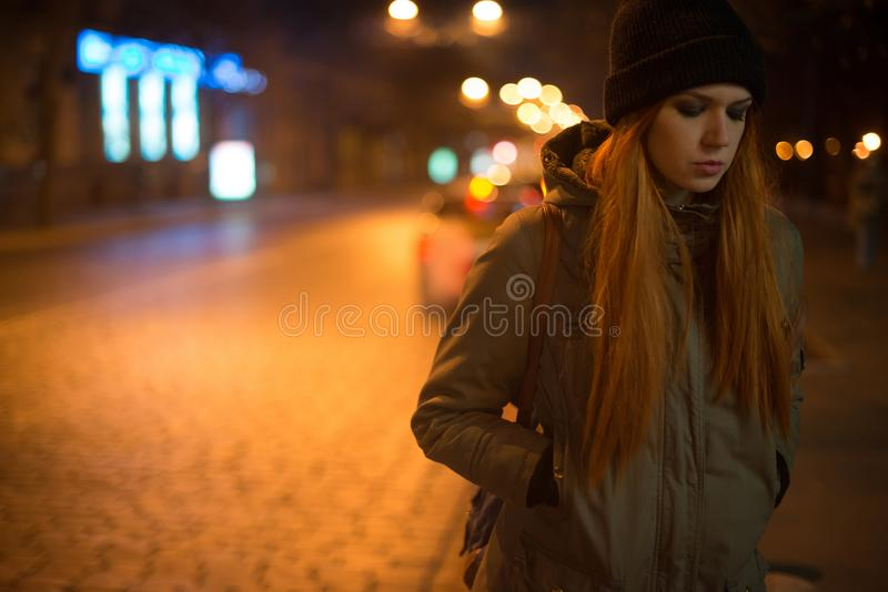 Young beautiful girl catches a taxi in the city street at night.  royalty free stock photography