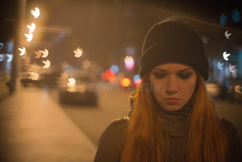 Young beautiful girl catches a taxi in the city street at night.  stock image
