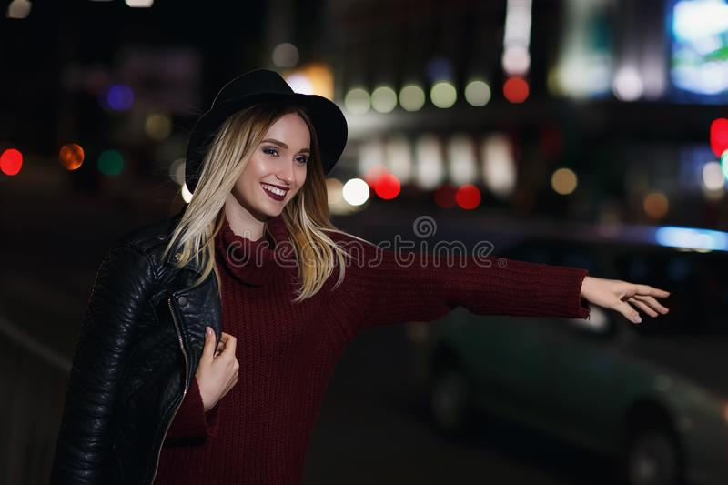 Young beautiful girl catches a taxi stock photography