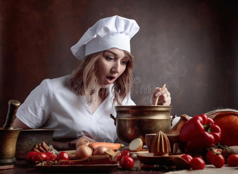 Young beautiful girl in a chef uniform with old brass pan and w royalty free stock photo