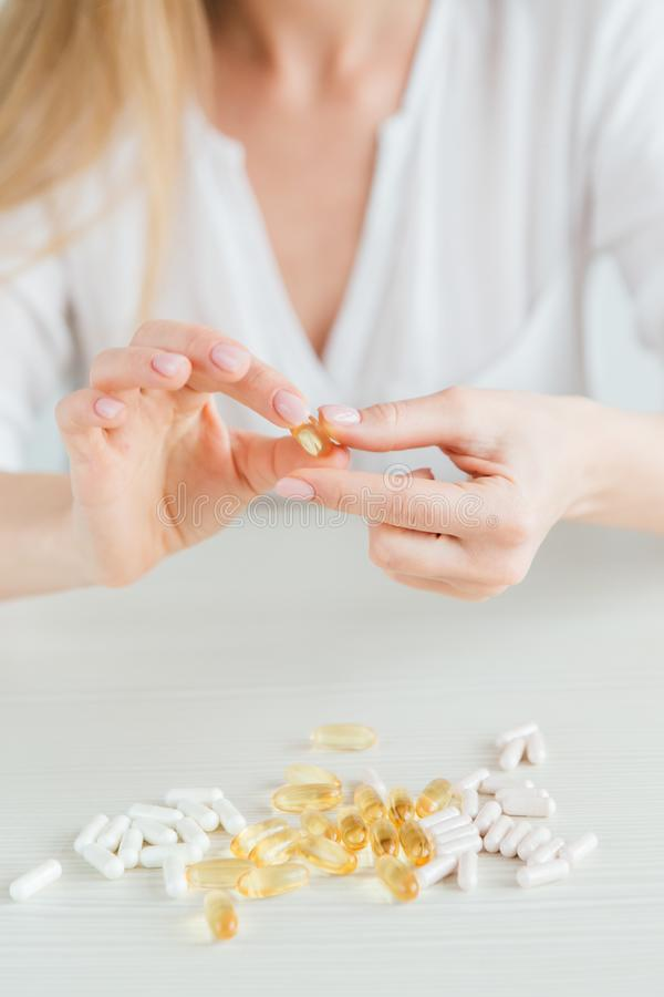 Young beautiful girl chooses pills, colorful capsules of tablets, vitamins, dietary supplements stock photography