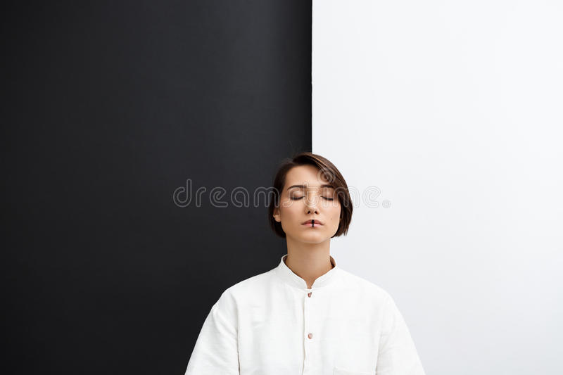 Young beautiful girl with closed eyes over black and white background. stock photos