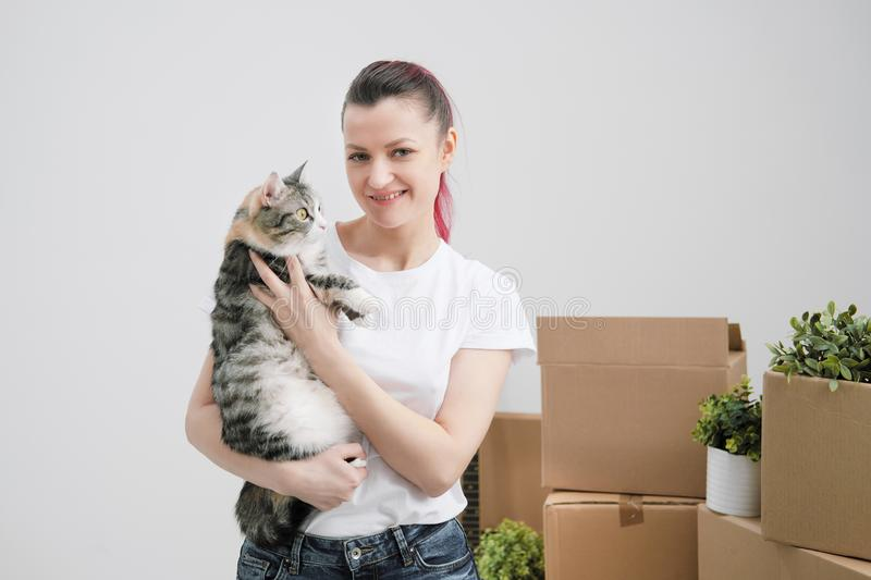 Young beautiful girl with colored hair in a white T-shirt and jeans, holding a pet cat and looking out the window stock photography