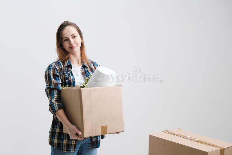 Young beautiful girl with colored hair in a white T-shirt, plaid shirt and jeans, against the background of cardboard stock photography