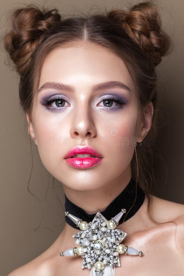 Young beautiful girl with the colorfull make-up, perfect skin, bunches hairstyle. Pink lips. Choker on a neck royalty free stock image