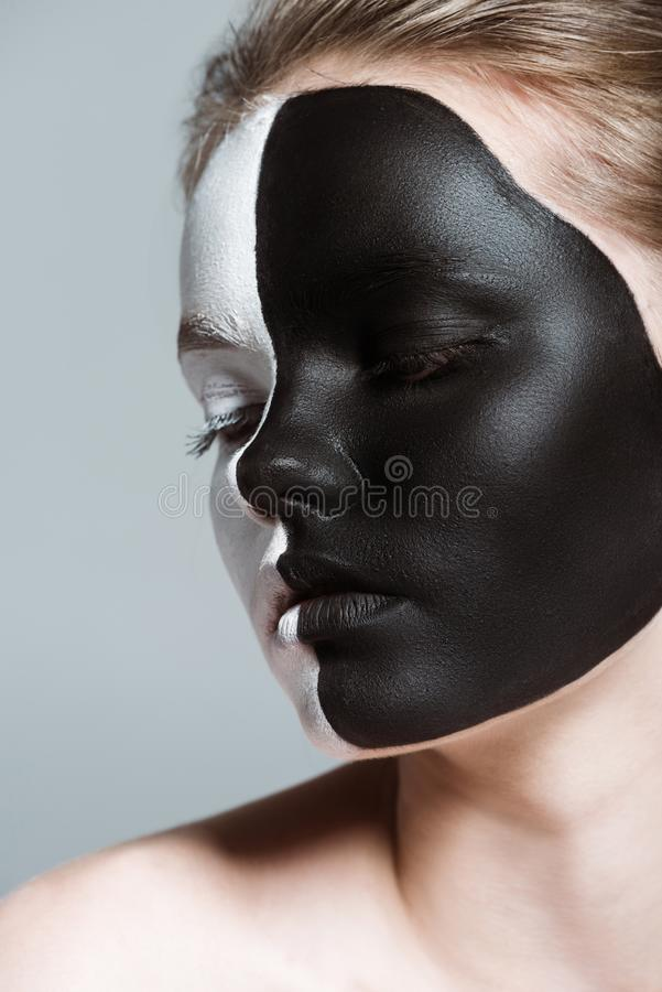young beautiful girl with creative white and black bodyart on face, stock image