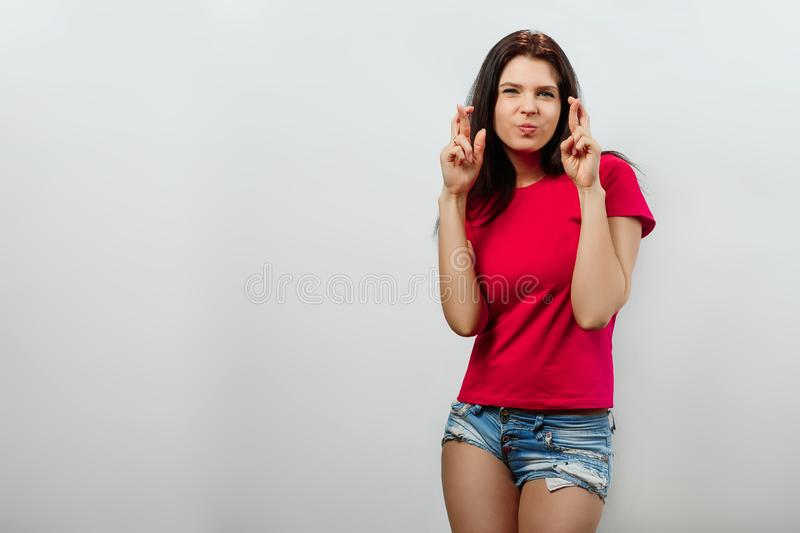 A young, beautiful girl crossed her fingers. Isolated on a light background. Different human emotions, feelings of facial stock photos