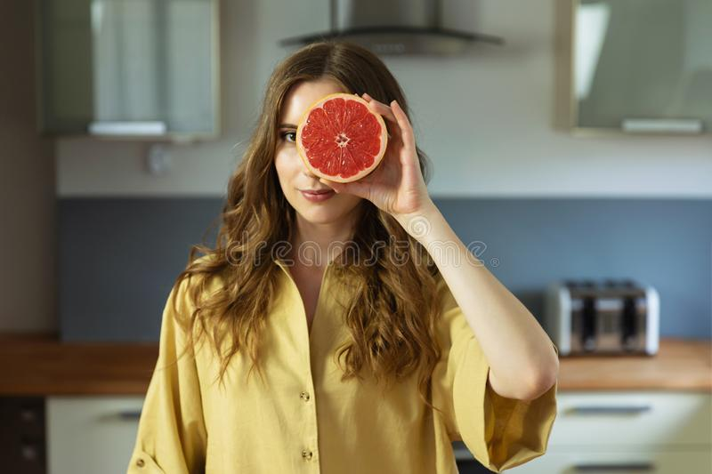 A young beautiful girl cuts a grapefruit, she has fun and closes one eye with half a grapefruit. royalty free stock images
