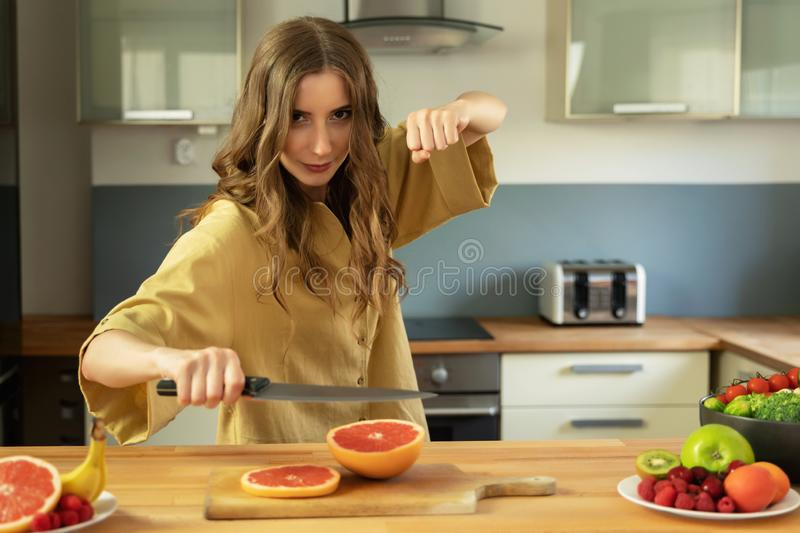 A young beautiful girl cuts a grapefruit, she has fun and pretends to be a ninja warrior. stock photography