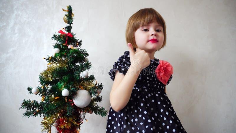 Young beautiful girl dancing next to Christmas tree. royalty free stock photo