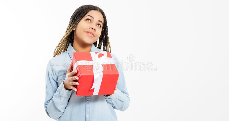 Young beautiful girl in denim shirt holds a big gift box and looks up on a white background.  royalty free stock photography