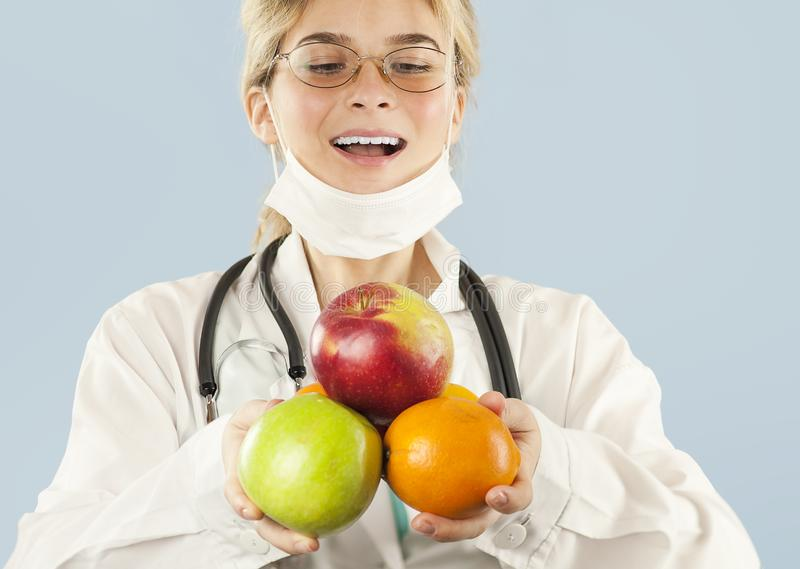 Beautiful girl doctor nutritionist with fruit in hand on blue isolated background. Healthy eating concept royalty free stock image