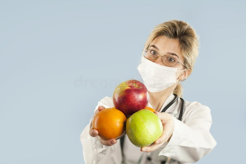Beautiful girl doctor nutritionist with fruit in hand on blue isolated background. Healthy eating concept stock images