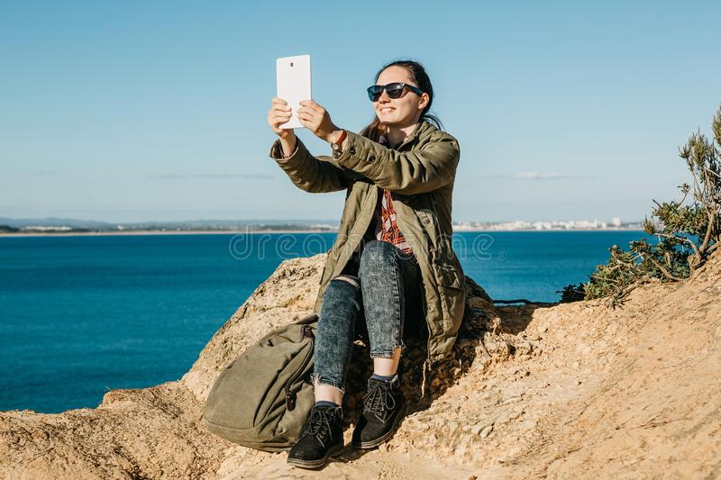 A young beautiful girl does selfie or talks by using a tablet online or takes pictures of a beautiful landscape.  royalty free stock photography