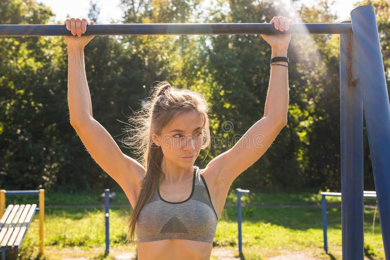 Active and young woman doing pullups. Young beautiful girl doing chin-ups on the outdoor sports ground stock photography