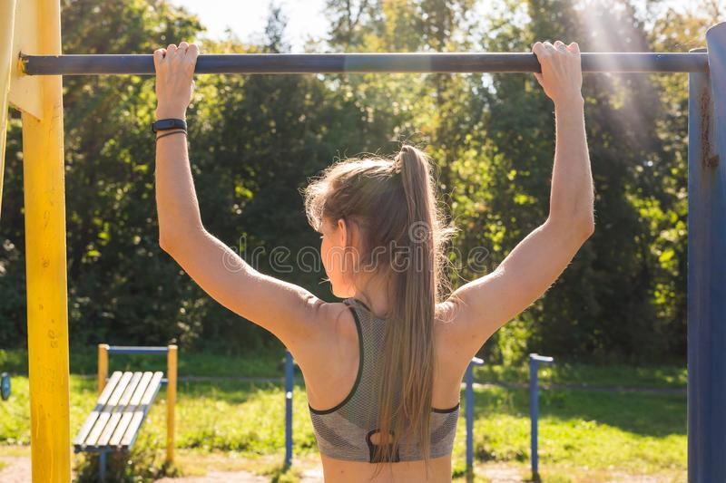 Active and young woman doing pullups. Young beautiful girl doing chin-ups on the outdoor sports ground royalty free stock photos
